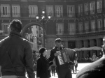 An accordion player delights one of many tourists in the Plaza Mayor