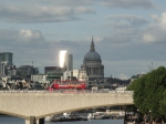 Iconic London - red bus, St Paul's and the sun reflecting off a skyscraper